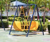 stock photo of swingset  - Yellow Swing on Children Playground, Close-up on sunny day