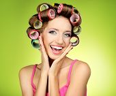 image of hair curlers  - Beautiful girl in hair curlers on green background - JPG