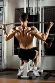 image of execution  - very power athletic guy bodybuilder execute exercise with gym apparatus on broadest muscle of back - JPG