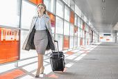 foto of carry-on luggage  - Full length of young businesswoman with luggage walking in railroad station - JPG