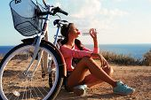 picture of sportive  - fashion outdoor photo of pretty young brunette wearing sportive clothes and drinking water sitting beside a bicycle on beach - JPG