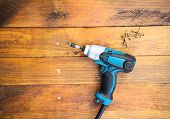 stock photo of wood craft  - Close up electric drill and nails left on wooden floor - JPG
