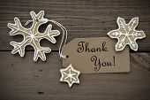 image of ginger bread  - Brown Banner with Thank You on it and Ginger Bread Snowflakes with white Decoration on Wooden Background - JPG