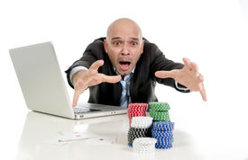 picture of addicted  - desperate addict businessman on computer laptop loosing lots of money betting on internet poker with cards and chips on online gambling addiction isolated on white - JPG
