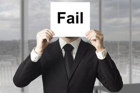 stock photo of fail job  - businessman in black suit hiding face behind sign fail - JPG