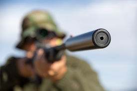 picture of gunshot  - Man aiming his rifle with suppressor at target  - JPG