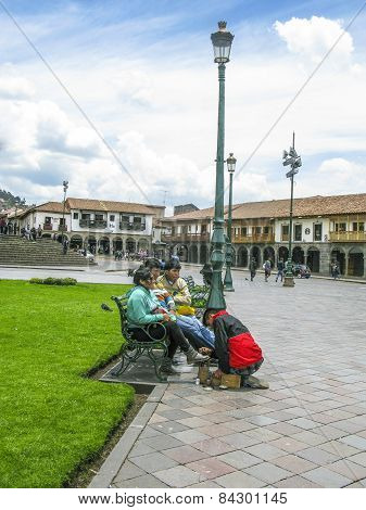 Shoe Cleaner Cleans Shoes From Local People At Central Square In Cuzco, Plaza De Armas.