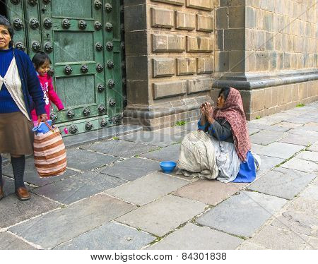 Poor People Beg For An Alm In Front Of The Basilica De La Cathedral