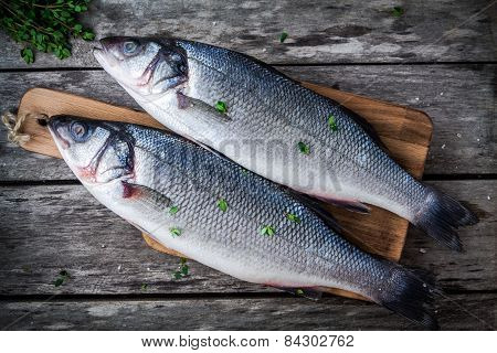 Two Raw Fresh Sea Bass On A Cutting Board With Thyme