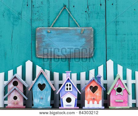 Blank sign hanging over fence and row of birdhouses