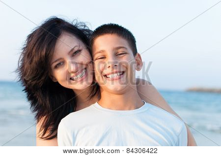 Mother with her son are having fun on the beach