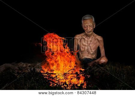 Old Man Sitting Next To A Fire
