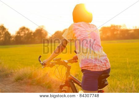 Girl Cycling In Rice Fields.