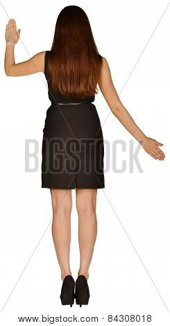beautiful woman in a dress stands back and raised her arms to the side.