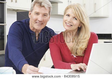 Smiling Mature Couple Reviewing Domestic Finances