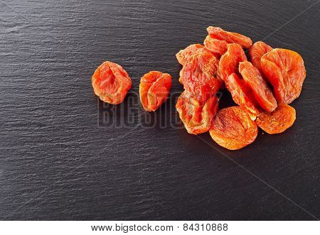 A Heap Of Dried Apricots On A Dark Background