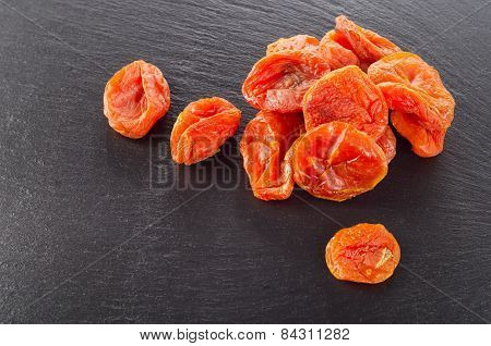 A Heap Of Dried Apricots On  Dark Background