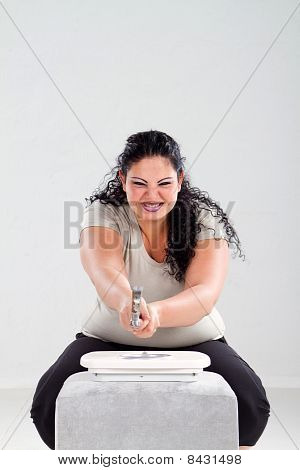 overweight woman smashing scale