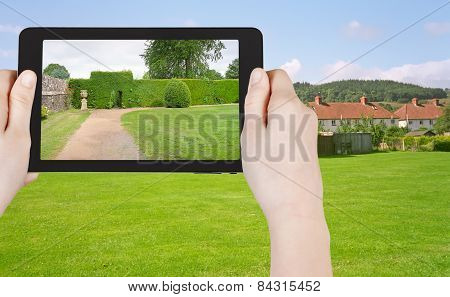 Tourist Taking Photo Of Green Lawn In England