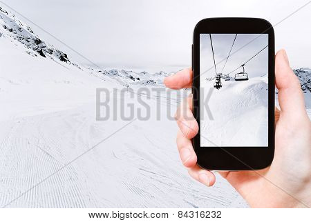 Tourist Taking Photo Of Skiing Tracks And Ski Lift