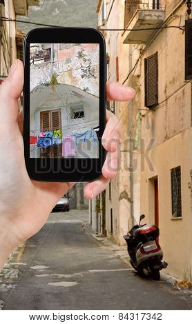 Tourist Taking Photo Of Side Street In Town
