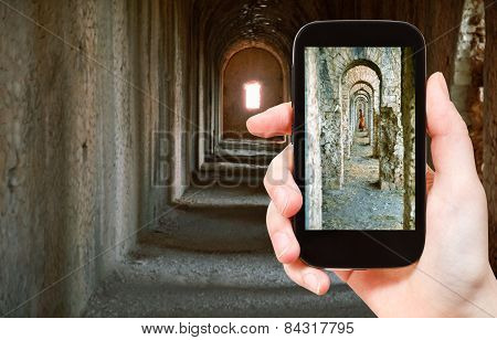 Tourist Taking Photo Of Ancient Arcades In Temple