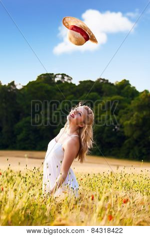 Beautiful Young Blonde Scottish Girl In White Dress At Golden Wheat Field Catching Her Straw Hat