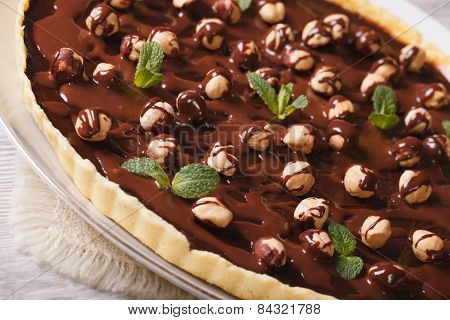 Tart With Chocolate And Hazelnuts On A Table Closeup. Horizontal