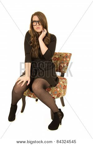 Younger Female Model Sitting With A Serious Expression