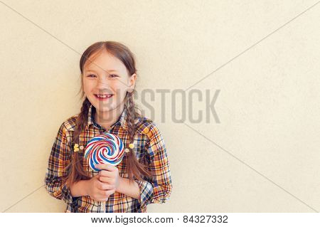 Portrait of a cute little girl of 7 years old, holding big colorful candy, wearing plaid shirt