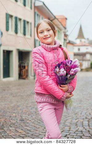 Spring portrait of adorable little girl of 7 years old, wearing bright pink coat, holding beautiful