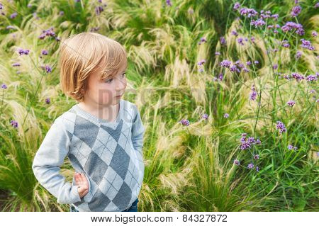 Adorable blond toddler boy playing in a garden, wearing grey pullover