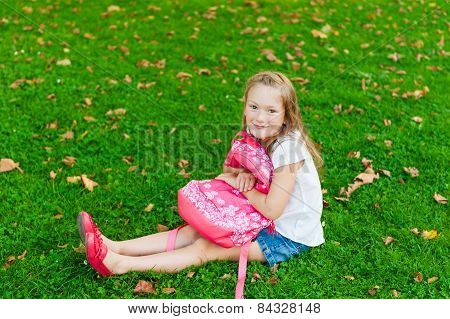 Little girl resting in a park after school