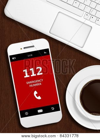 Mobile Phone With Emergency Number 112 Lying On Desk