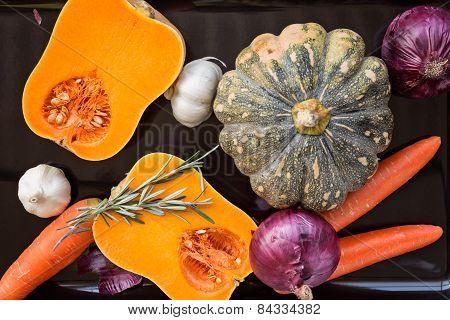 Pumpkin, Carrot, Onion, Garlic And Rosemary On Black Tray Ready To Roast