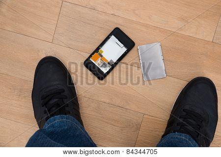 Person Standing Near Broken Cellphone
