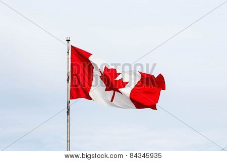 Canadian Flag Flying Under Clouds