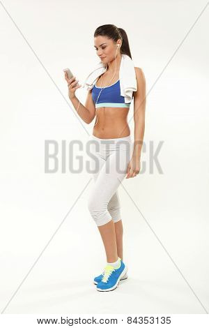 Beautiful Young Woman In Sports Equipment Listens To Music