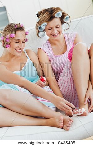 Positive Female Friends Doing Pedicure And Wearing Hair Rollers