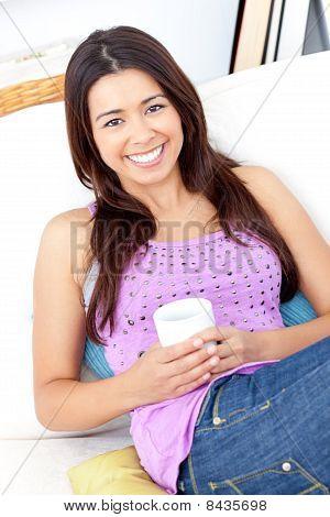 Mulher brilhante, segurando uma xícara de café sorrindo para a câmera