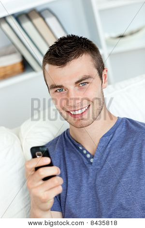Charming Young Man Sending A Text Smiling At The Camera