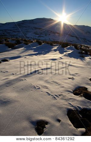 Sun burst star over the snow in Lesotho.