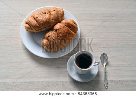 Cup Of Black Coffee Served With Two Croissants