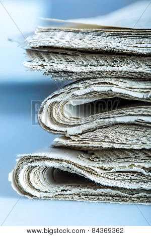 Newspapers folded and stacked concept for global communications.