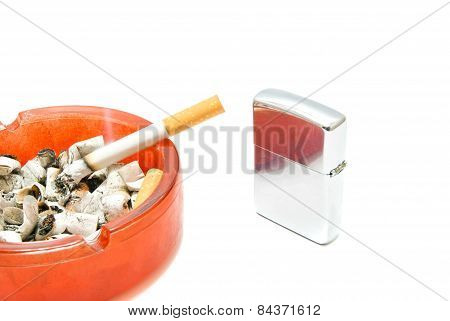 Metal Lighter And Cigarette In Red Ashtray