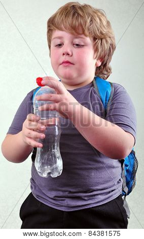 Cute Blond Schoolboy With A Bottle Of Water