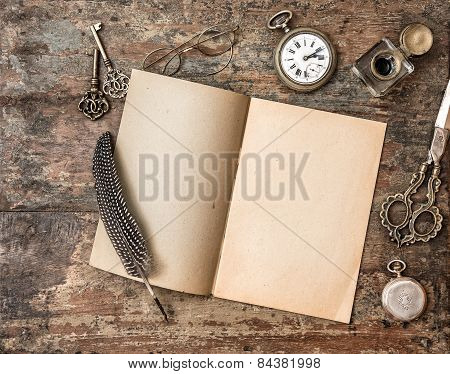 Open Book And Vintage Writing On Wooden Table