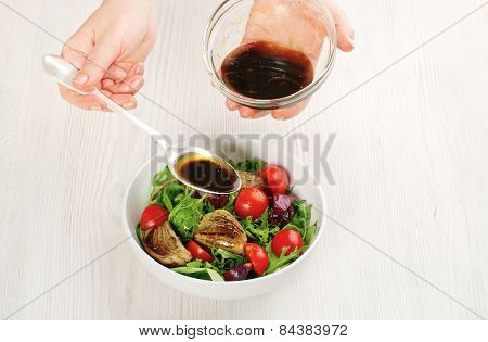 Pouring Salad With Sauce