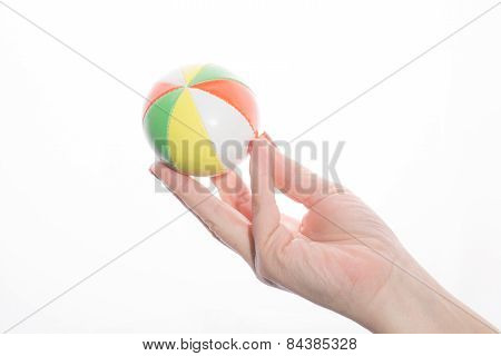 female hand holding colored juggling balls on a white background
