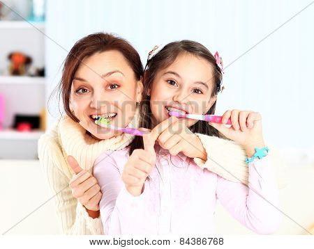 Mother and daughter brush their teeth.